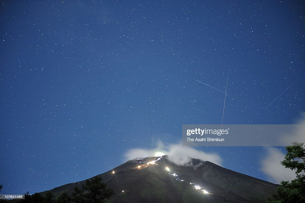 In this long exposure image, Perseid Meteor Showers are observed above Mt. Fuji on August 13, 2009 in FUjiyoshida, Yamanashi, Japan.