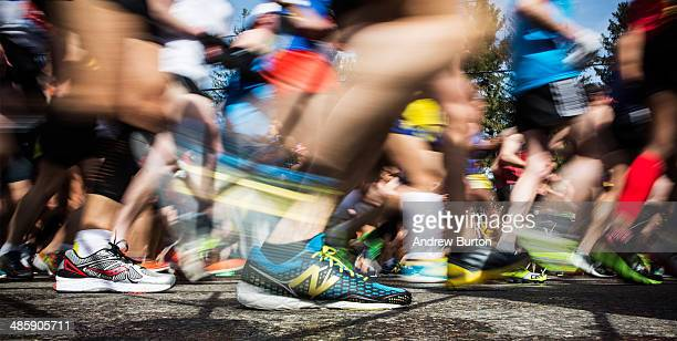In this long exposure photograph runner's shoes are seen at the beginning of the Boston Marathon on April 21 2014 in Hopkington Massachusetts Today...