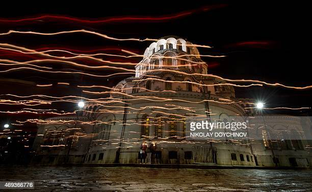 In this long exposure picture Bulgarian Orthodox worshipers walk with candles in front of the Alexander Nevsky Cathedral in Sofia on April 11 2015...