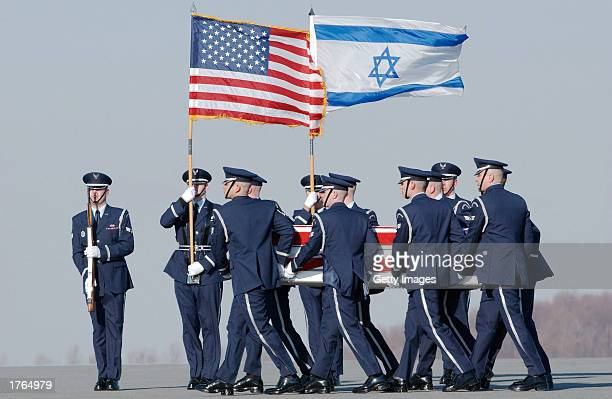 In this NASA handout image an Air Force honor guard led by the flags of the United States of America and the nation of Israel carries a casket...