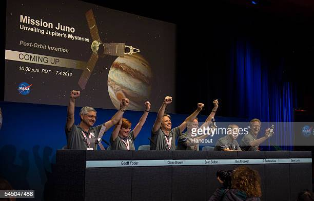 In this NASA handout Members of the Juno team celebrate at a press conference after they received confirmation from the Juno spacecraft that it had...