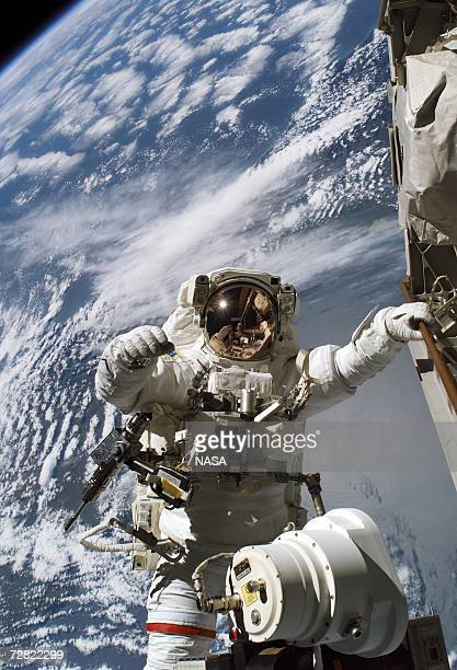 In this NASA handout photo astronaut Robert L Curbeam Jr STS116 mission specialist prepares to replace a faulty TV camera on the exterior of the...