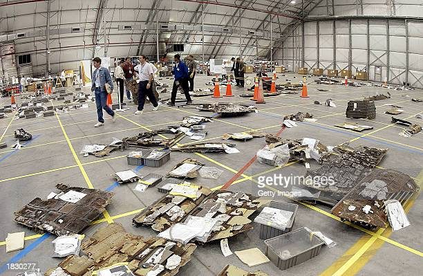 In this NASA photo NASA crash investigators place debris from the Space Shuttle Columbia on a grid on the floor of a hangar on March 4 2003 at the...