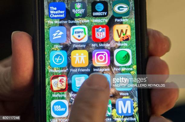In this November 1 2016 photo illustration a person points to the new Instagram app on a smartphone / AFP / ANDREW CABALLEROREYNOLDS