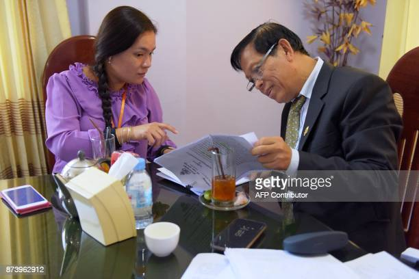 In this November 8 2017 photograph Lim Kimya a member of the National Assembly from Cambodia National Rescue Party confers with an assistant as they...