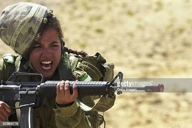 In this photo distributed by the Israeli Defense Forces May 23 a woman soldier is charges with an M16 assault rifle as her infantry instructors'...