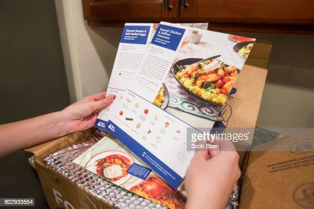 In this photo illustration a Blue Apron customer looks at recipes for the weeks meals from inside a Blue Apron box on a kitchen counter on June 28...