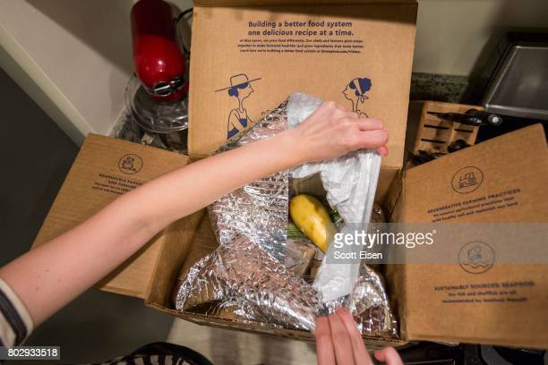 In this photo illustration a Blue Apron customer prepares to remove items from inside a Blue Apron box on June 28 2017 in Boston Massachusetts The...