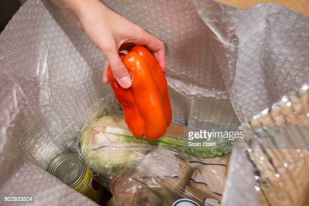 In this photo illustration a Blue Apron customer removes a pepper from inside a Blue Apron box on June 28 2017 in Boston Massachusetts The online...