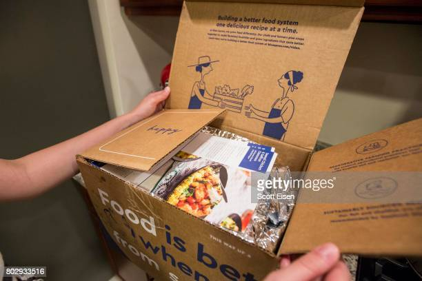 In this photo illustration a Blue Apron customer unpacks a Blue Apron box on a kitchen counter on June 28 2017 in Boston Massachusetts The online...