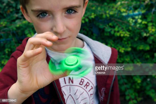 In this photo illustration a child spins a 'Hand Spinner' on May 20 2017 in Paris France The 'Hand Spinner' is a toy that sits like a propeller on a...