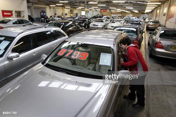 In this photo illustration a child views the interior of a luxury car on sale at Cargiant the world's largest car supermarket in White City on...