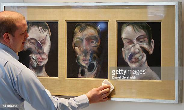 In this photo illustration A Christies employee cleans a painting by Francis Bacon called Three Studies for a Self Portrait during a viewing at...
