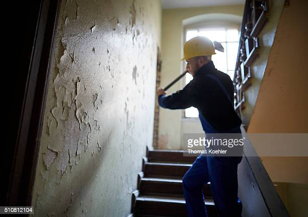 In this Photo Illustration a construction worker removes plaster from the wall in a staircase during the renovation of an old building on February 03...