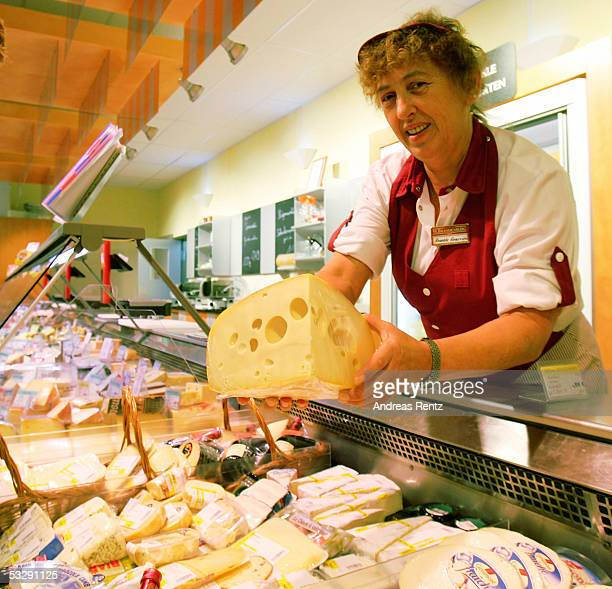 In this photo illustration a customer consultant of the cheese department shows a big piece of Holland cheese in a supermarket July 26 2005 in...