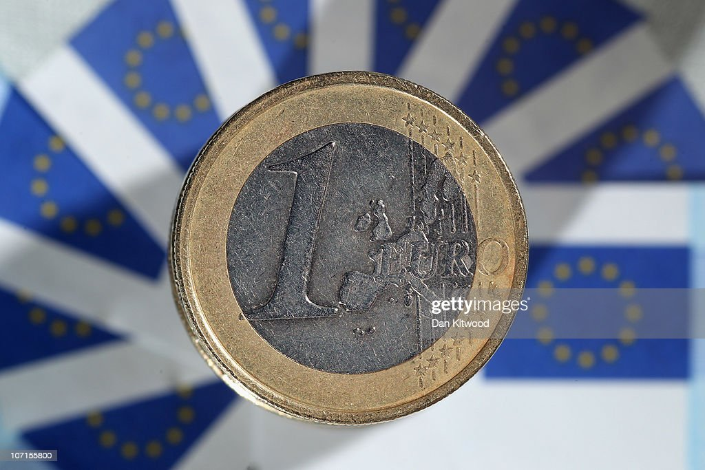 In this photo illustration a GBP1 coin sits on a display of 5 Euro notes on November 26 2010 in London England Concerns over the Euro zone debts have...