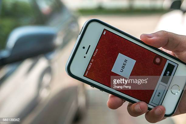 Hand holding a smart phone with Uber App Uber is selling its operation in China to its chief rival Didi Chuxing in exchange for a 20 percent stake...