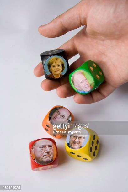 In this photo illustration a hand holds dice showing the portraits of the leading candidates for the German federal election 2013 Angela Merkel Peer...