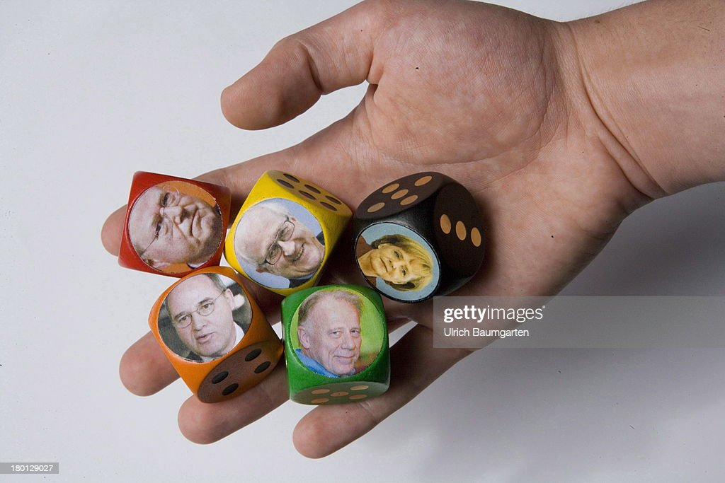 In this photo illustration, a hand holds dice showing the portraits of the leading candidates for the German federal election 2013, Angela Merkel (CDU), Peer Steinbrueck (SPD), Juergen Trittin (Alliance 90/The Greens), Rainer Bruederle (FDP) and Gregor Gysi (Die Linke), on August 14, 2013 in Bonn, Germany.