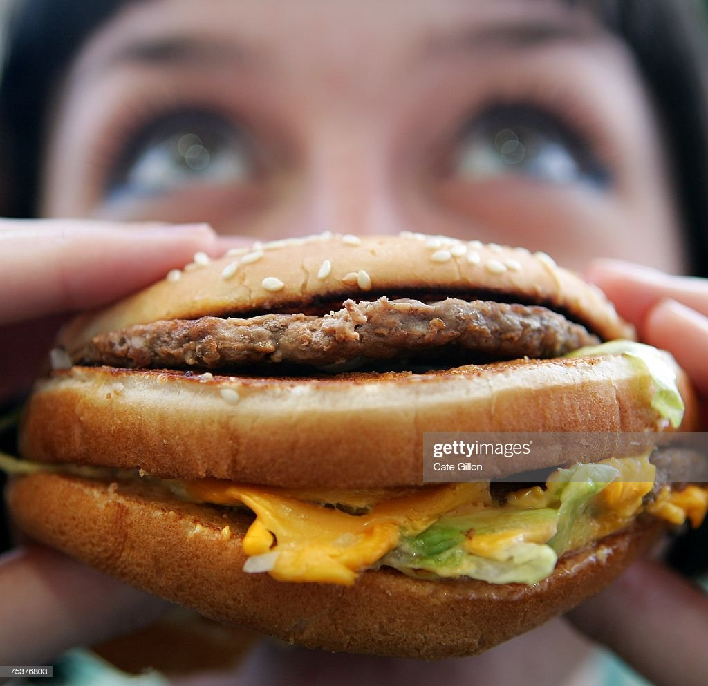In this photo illustration a lady eats a beefburger on July 12, 2007 in London, England. Government advisors are considering plans for a fat tax on foods high in fat to try to help tackle the fight against obesity.
