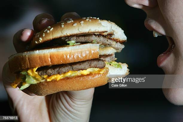 In this photo illustration a lady eats a beefburger on July 12 2007 in London England Government advisors are considering plans for a fat tax on...