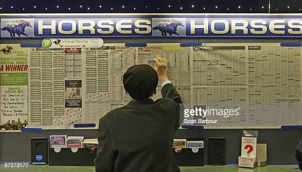 In this photo illustration a man checks the form as he places a bet ahead of this weekend's Grand National at a betting shop on April 7 2006 in...