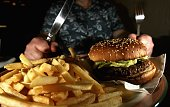 In this photo illustration a man eats a hamburger ind chips in a cafe on June 72006 in Glasgow Scotland New figures are suggesting that a large...