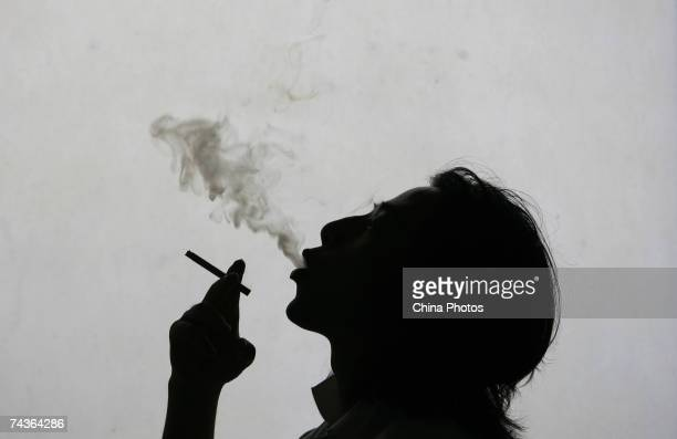 In this photo illustration a man exhales smoke whilst smokign a cigarette on World No Tobacco Day May 31 2007 in Nanjing China About 540 million...