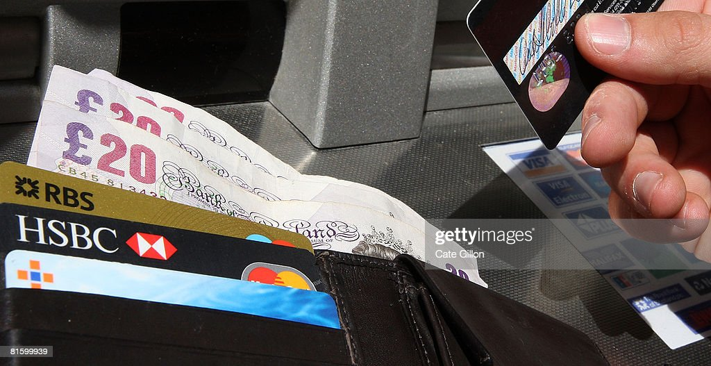 In this photo illustration a man holds a card and his wallet by an ATM bank machine on June 17, 2008 in London, England. The governor of the Bank of England has stated that inflation could rise above 4% this year as a result of increasing prices of energy and food.