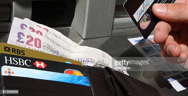 In this photo illustration a man holds a card and his wallet by an ATM bank machine on June 17 2008 in London England The governor of the Bank of...