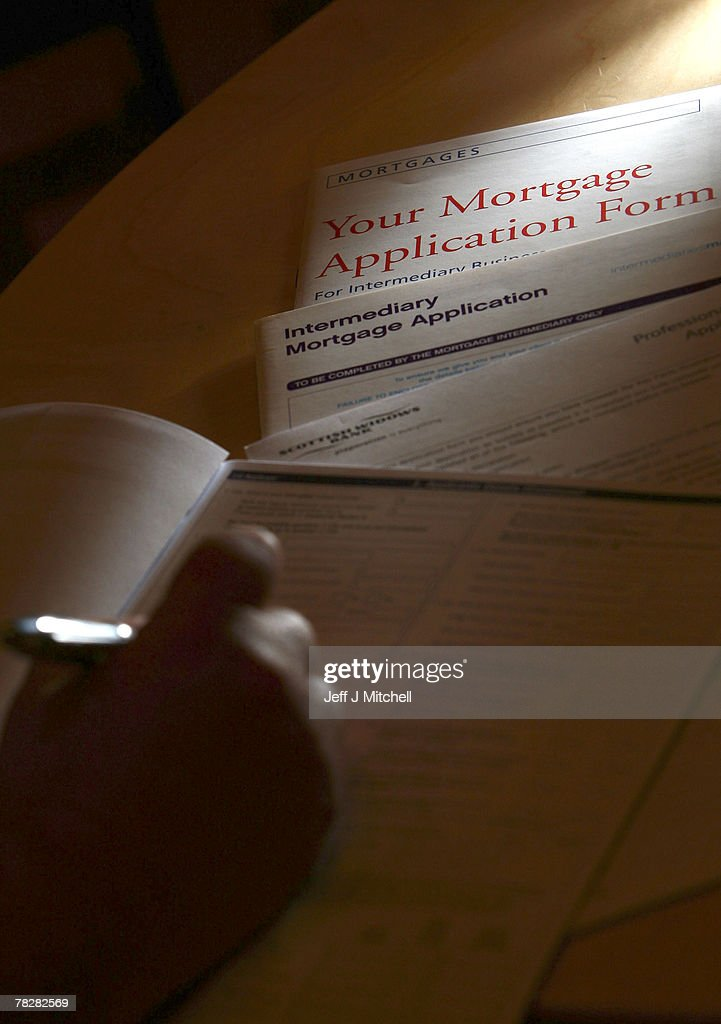In this photo illustration a man holds a pen over mortgage application forms December 6, 2007 in Glasgow,Scotland.The British economy is beginning to feel the effects of the credit crisis which began this year. House prices have begun to fall and the retail sector is predicting a difficult Christmas period.