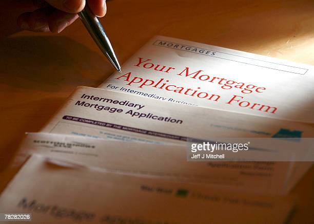In this photo illustration a man holds a pen over mortgage application forms on December 6 2007 in GlasgowScotlandThe British economy is beginning to...