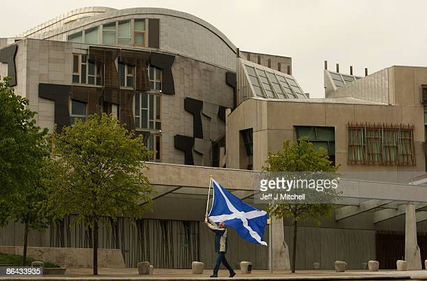 In this photo illustration A man holds a Saltire flag outside the Scottish Parliament on May 6 2009 in Edinburgh Scotland Today marks the 10th...