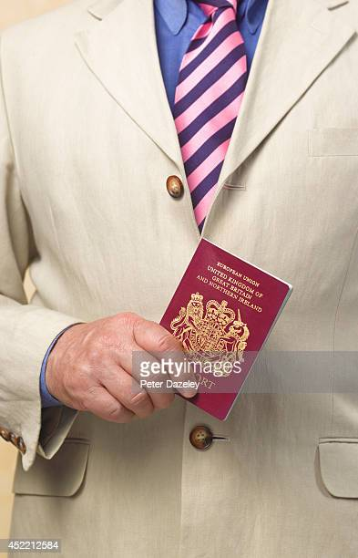 In this photo illustration a Man holds a United Kingdom passport on July 2014 in LondonEngland