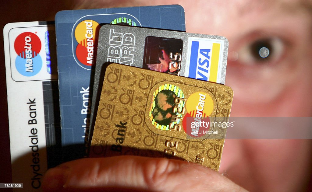 In this photo illustration a man holds up some credit and debit cards on December 6, 2007 in Glasgow,Scotland.The British economy is beginning to feel the effects of the credit crisis which began this year. House prices have begun to fall and the retail sector is predicting a difficult Christmas period.