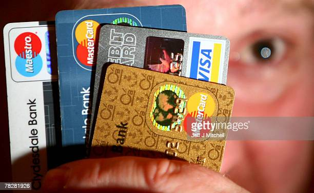 In this photo illustration a man holds up some credit and debit cards on December 6 2007 in GlasgowScotlandThe British economy is beginning to feel...