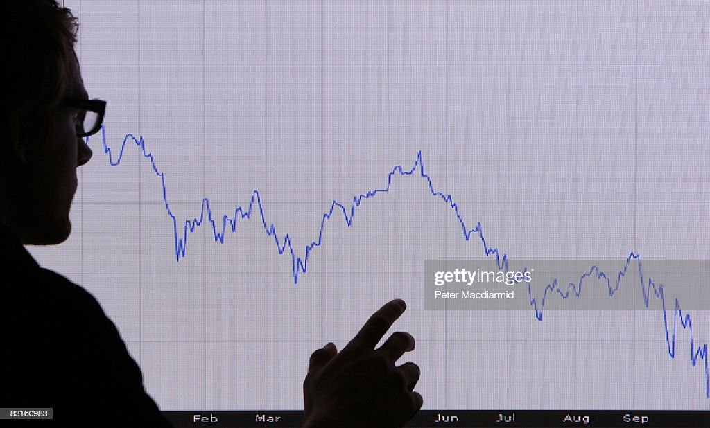 In this photo illustration, a man looks at a graph representing the 12 month decline of the FTSE 100 share index on October 7, 2008 in London. Financial markets are still suffering large losses as the global banking crisis continued.