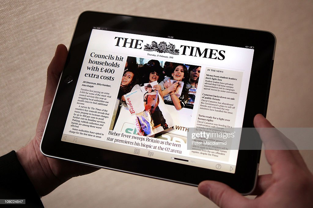 In this photo illustration a man looks at The Times app on an Apple ipad tablet on February 17 2011 in London England Apple sold two million ipads in...