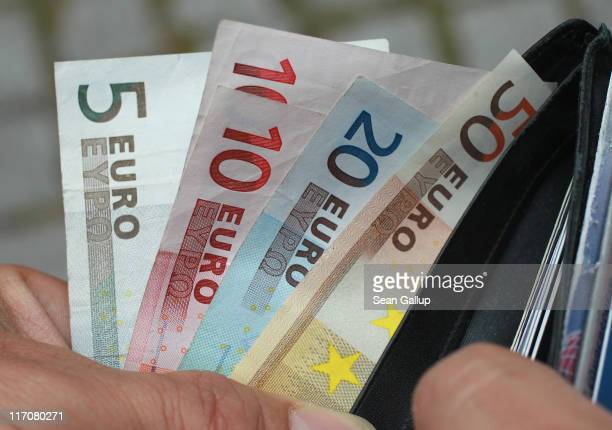 In this photo illustration a man removes Euro currency bills from a wallet on June 21 2011 in Berlin Germany Eurozone finance ministers are currently...