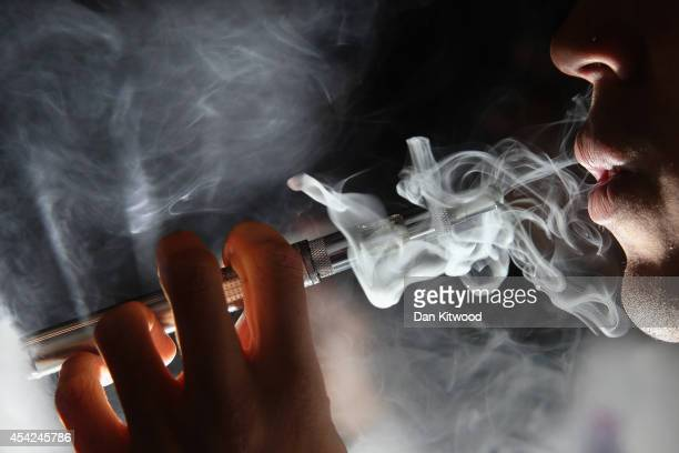 In this photo illustration a man smokes an ECigarette at the VRevolution ECigarette shop in Covent Garden on August 27 2014 in London England The...