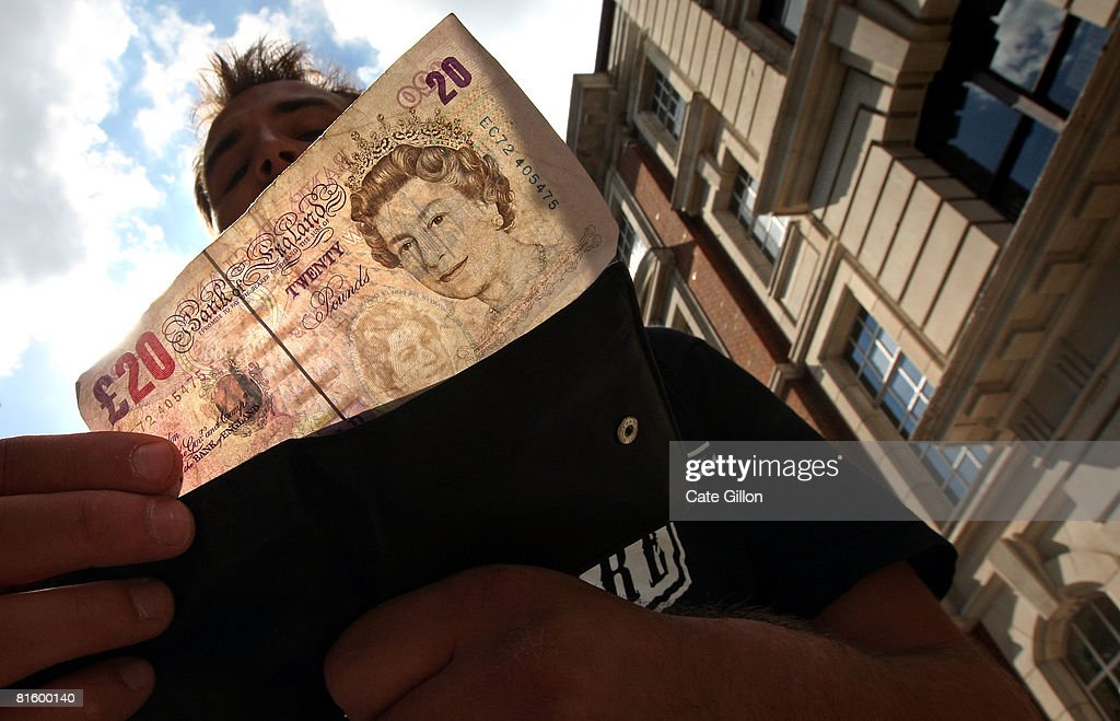 In this photo illustration, a man takes a 20 pound note from his wallet outside a bank on June 17, 2008 in London, England. The governor of the Bank of England has stated that inflation could rise above 4 percent this year as a result of increasing prices of energy and food.
