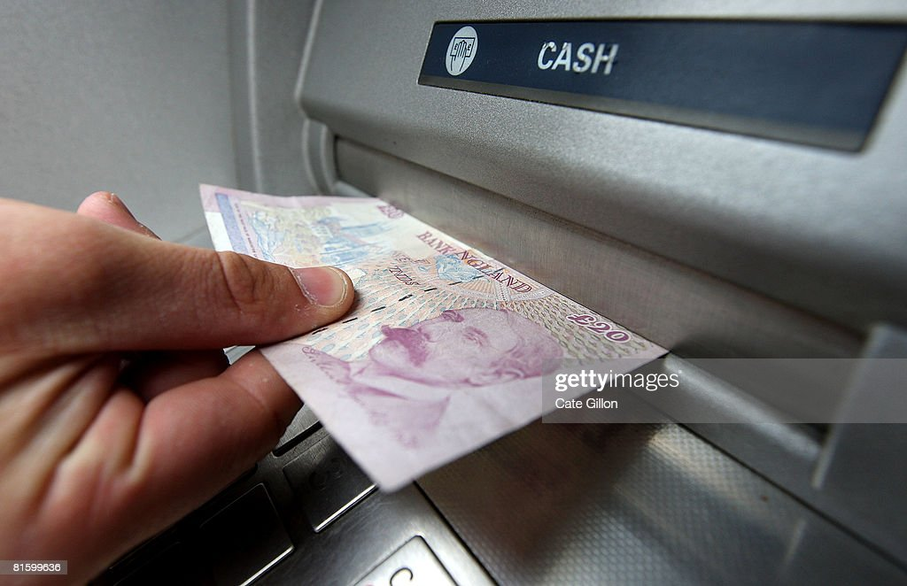 In this photo illustration a man takes a twenty pound (GPB) note from an ATM bank machine on June 17, 2008 in London, England. The governor of the Bank of England has stated that inflation could rise above 4% this year as a result of increasing prices of energy and food.