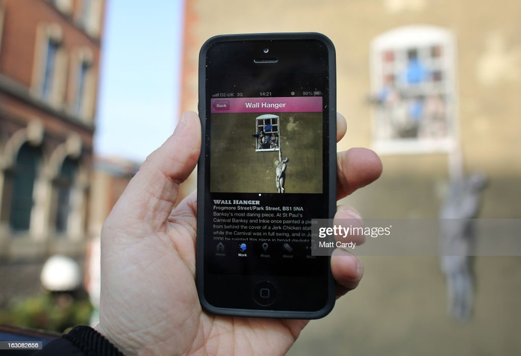 In this photo illustration a man uses an app on his iPhone to look atbuildiong Extr a mural by the street artist Banksy which has been defaced by blue paint bombs is seen on the side of a building in Park Street on March 4, 2013 in Bristol, England. The Twentieth Century Society has launched a campaign to try and save some of the UK's best known post-war murals which like much of the early artwork of graffiti artist Banksy has been destroyed, defaced or just left to deteriorate.