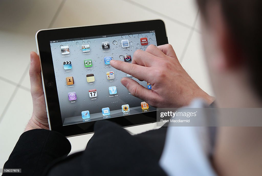 In this photo illustration, a man uses an Apple ipad tablet on February 17, 2011 in London, England. Apple sold two million ipads in the first two months of their launch in 2010. Worldwide iPad sales are expected to amount to 20 million in 2012.