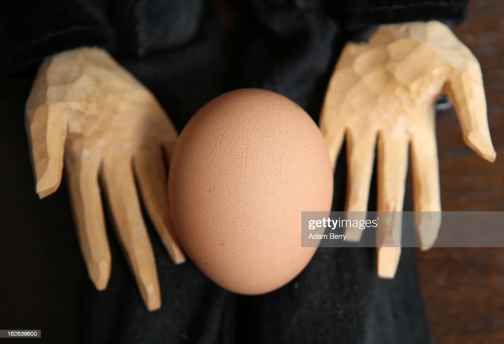 In this photo illustration, a marionette holds an egg sold as organic on February 25, 2013 in Berlin, Germany. According to a report, hundreds of egg-providing companies in the country are inaccurately describing their products as organic ('bio' in German), a mislabeling due to the producers exceeding the permitted maximum number of chickens allowed to be kept in their cages at one time to be able to receive the official certification.