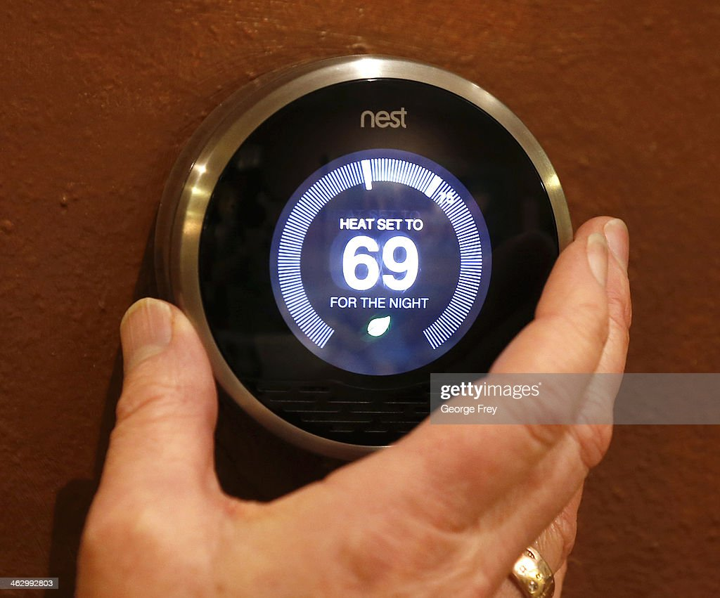 In this photo illustration, a Nest thermostat is being adjusted in a home on January 16, 2014 in Provo, Utah. Google bought Nest, a home automation company, for $3.2 billion taking Google further into the home ecosystem.