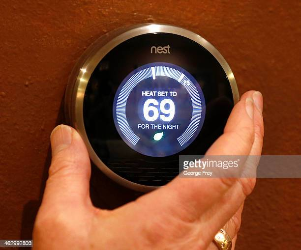 In this photo illustration a Nest thermostat is being adjusted in a home on January 16 2014 in Provo Utah Google bought Nest a home automation...