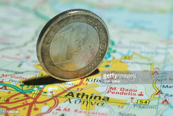 In this photo illustration a one Euro coin stands on a map of Greece showing the city of Athens on June 21 2011 in Berlin Germany Eurozone finance...