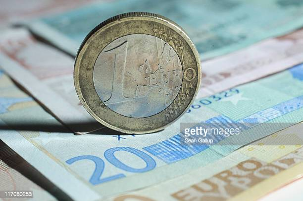 In this photo illustration a one Euro coin stands on Euro currency bills on June 21 2011 in Berlin Germany Eurozone finance ministers are currently...