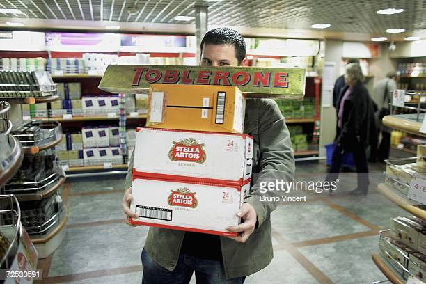 In this photo illustration a passenger carries boxes of beer and wine with an extra large chocolate bar on top aboard a cross channel ferry bound for...